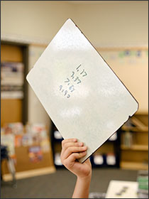 A fourth grade student holds up a dry erase board during a math lesson in the Bethel, Wash., district, which has adoped open ed. resources. --Ian C. Bates for Education Week