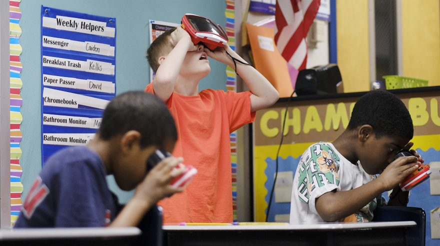 Tristin Dunkerson, center, uses a VR viewer to go on a virtual field trip to a rainforest in the classroom of teacher Amanda Moore at Chapelwood Elementary in Indianapolis. Moore uses Google Expeditions for the project, and she uses a variety of Google tools to communicate and share assignments with students. — AJ Mast for Education Week