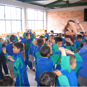 CEO Sara Potler LaHayne dances with students in Colombia.